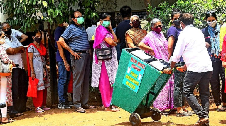 Mumbai: Ram Roti organisation provides free drinking water to people standing in queues for COVID-19 vaccine